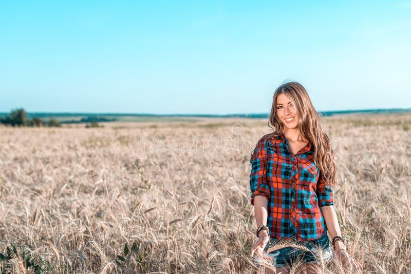 La muchacha feliz hermosa en el campo, tarde soleada, pone en cortocircuito la camisa El concepto de disfrutar de la naturaleza R foto de archivo libre de regalías