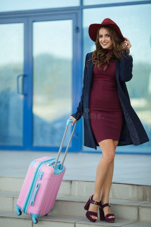 La muchacha feliz hermosa está llevando la ropa de la moda cerca de aeropuerto con la maleta Foto del concepto del viaje de la ge imagen de archivo libre de regalías