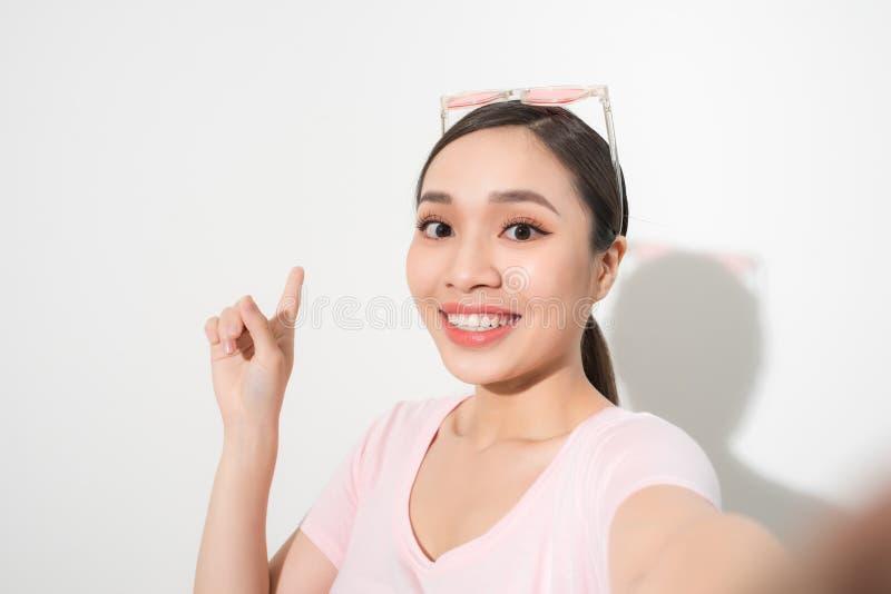 La muchacha feliz joven de la sonrisa toma el selfie en el fondo blanco imágenes de archivo libres de regalías