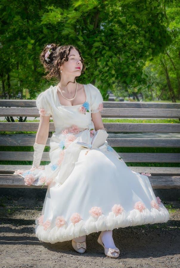 La muchacha feliz joven en un vestido blanco largo de la novia con una sonrisa es rea fotografía de archivo libre de regalías