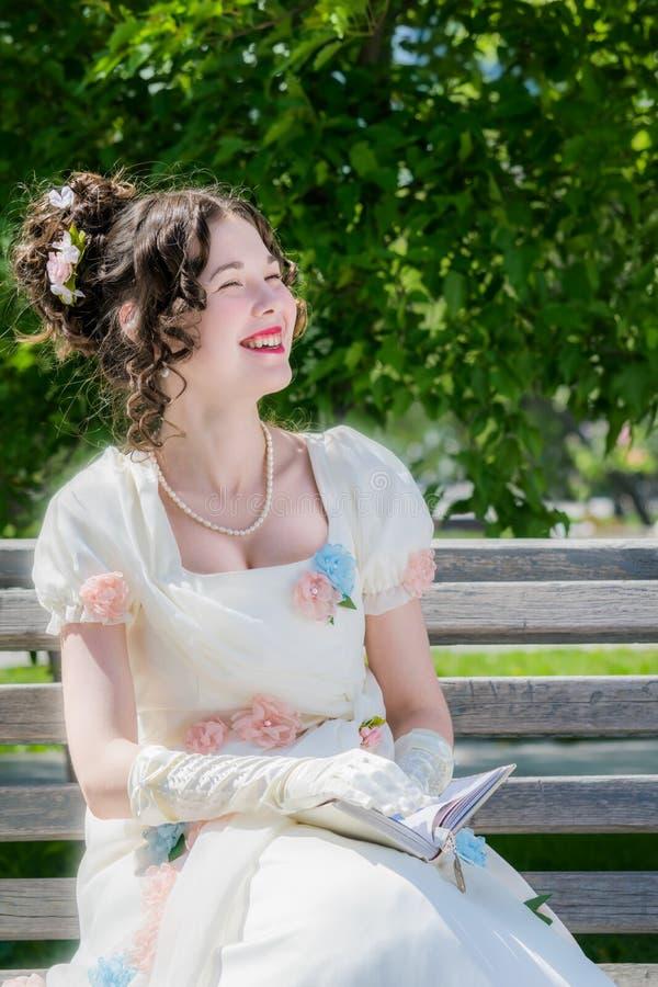 La muchacha feliz joven en un vestido blanco largo de la novia con una sonrisa es rea fotografía de archivo