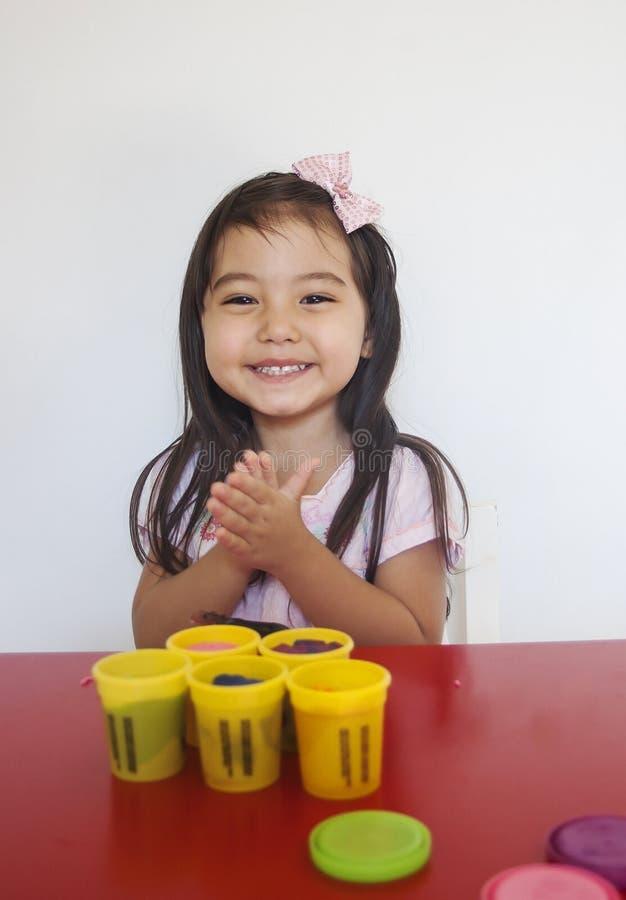 La muchacha feliz juega el playdough fotos de archivo libres de regalías