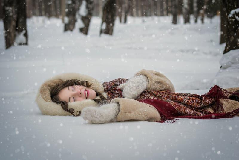 La muchacha feliz miente alrededor en nieve suave en un día de invierno imágenes de archivo libres de regalías