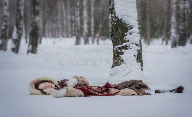 La muchacha feliz miente alrededor en nieve suave en un día de invierno foto de archivo libre de regalías