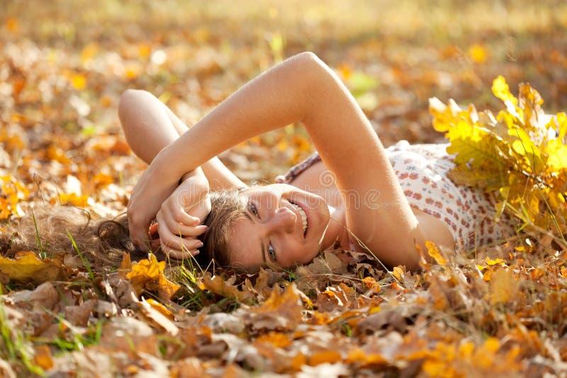 La muchacha feliz miente en parque del otoño imagenes de archivo