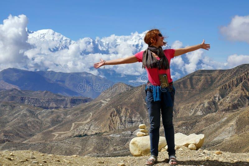 La muchacha feliz que la situación separó el suyo arma de par en par, contra el contexto de las montañas Himalayan imagen de archivo libre de regalías