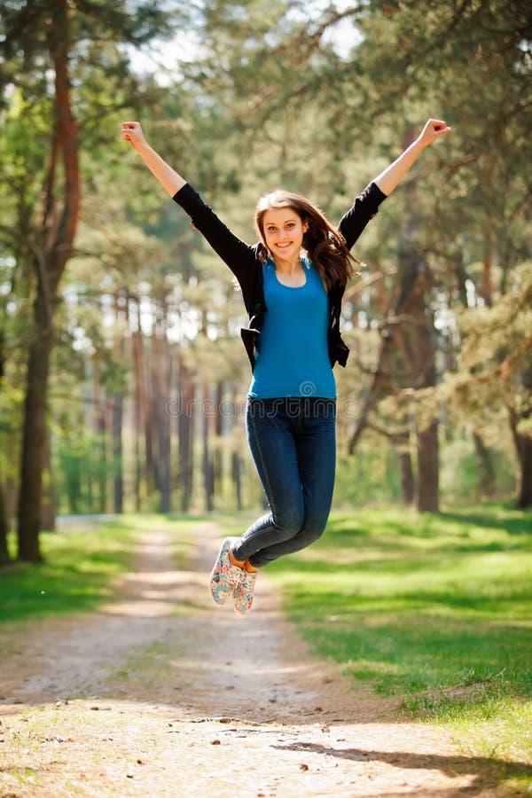 La muchacha feliz salta al aire libre en un park_vertical imágenes de archivo libres de regalías
