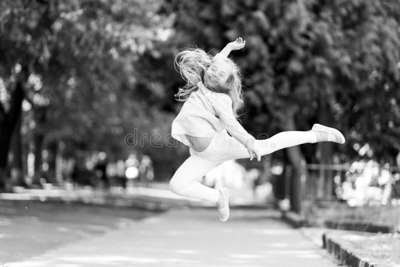 La muchacha feliz salta arriba en parque del verano Pequeña sonrisa del niño con el pelo del vuelo en el movimiento que siente li fotos de archivo