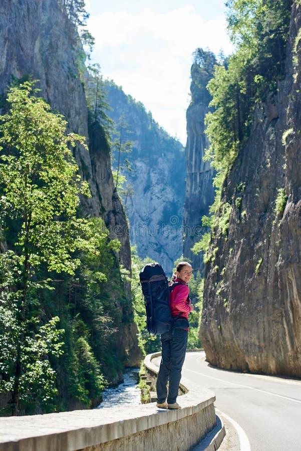 La muchacha feliz se coloca en el camino de la montaña de las montañas de Cárpatos del rumano fotografía de archivo