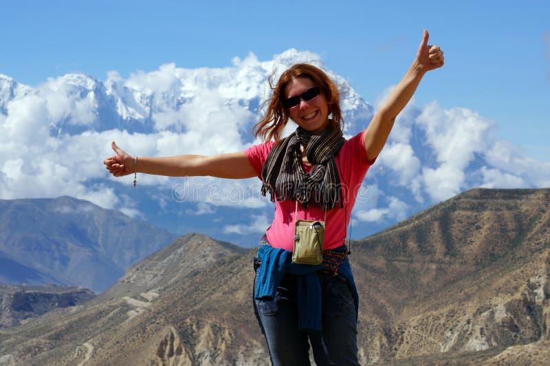 La muchacha feliz se está oponiendo, arma extendido, contra el contexto del macizo de Annapurna fotos de archivo libres de regalías