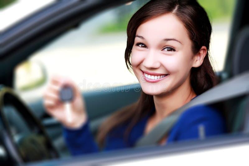 La muchacha feliz sonriente de los jóvenes hermosos muestra la llave del coche fotos de archivo
