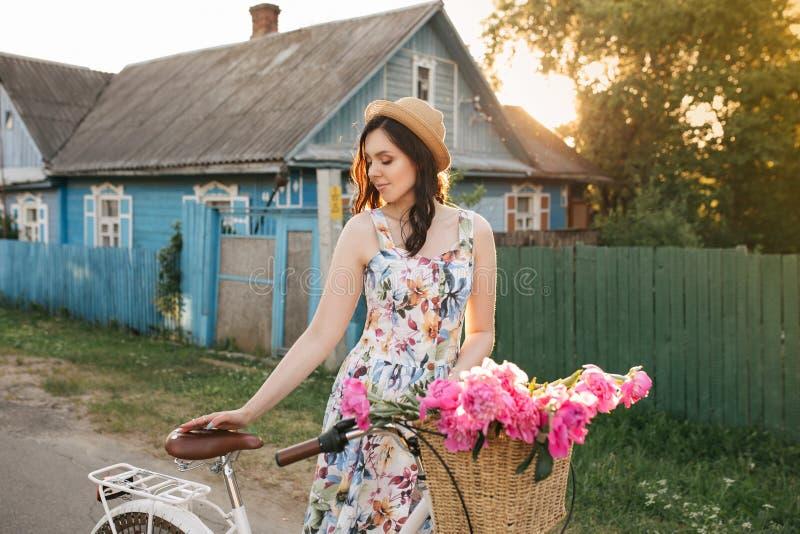 La muchacha feliz sonriente del brunnete en las blanco-flores se viste y sombrero con los peones rosados Sun está en el fondo fotos de archivo libres de regalías