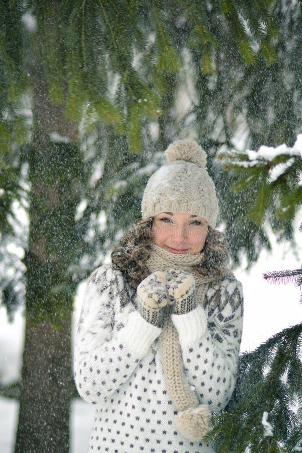 La muchacha feliz, sorprendente, asustada, afortunada, adorable en el bosque del invierno lleva a cabo su mano con las manoplas y fotos de archivo libres de regalías
