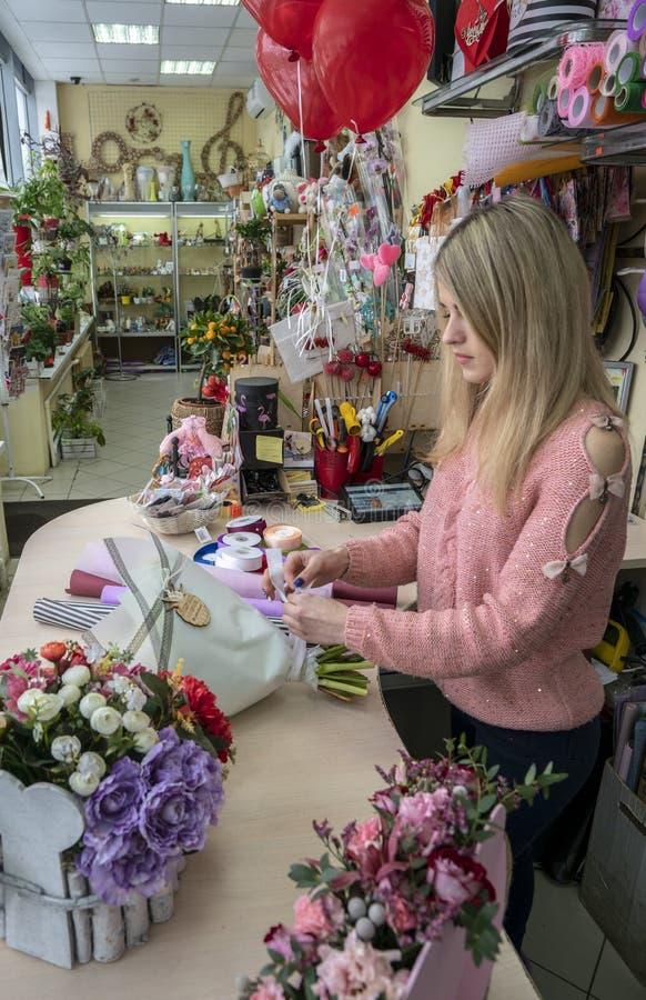 La muchacha, florista-diseñador hace un ramo hermoso, festivo de flores en una floristería imagen de archivo