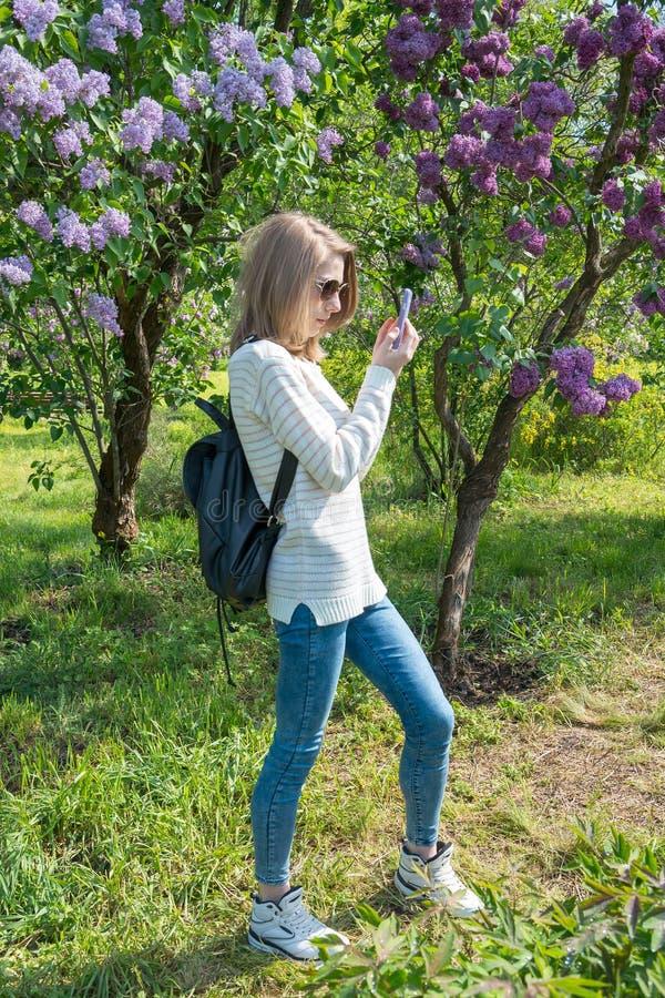 La muchacha fotografía la lila en el teléfono celular Chica joven que hace el selfie foto de archivo