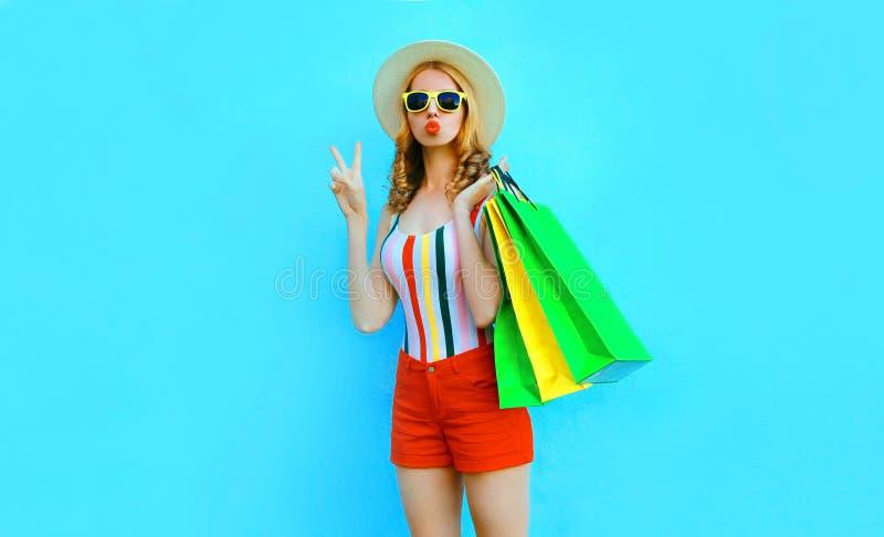 La muchacha fresca del retrato que sopla los labios rojos envía el beso del aire que presenta con los bolsos de compras en la ca foto de archivo