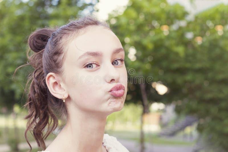 La muchacha guarda los labios como ir a besar alguien fotografía de archivo