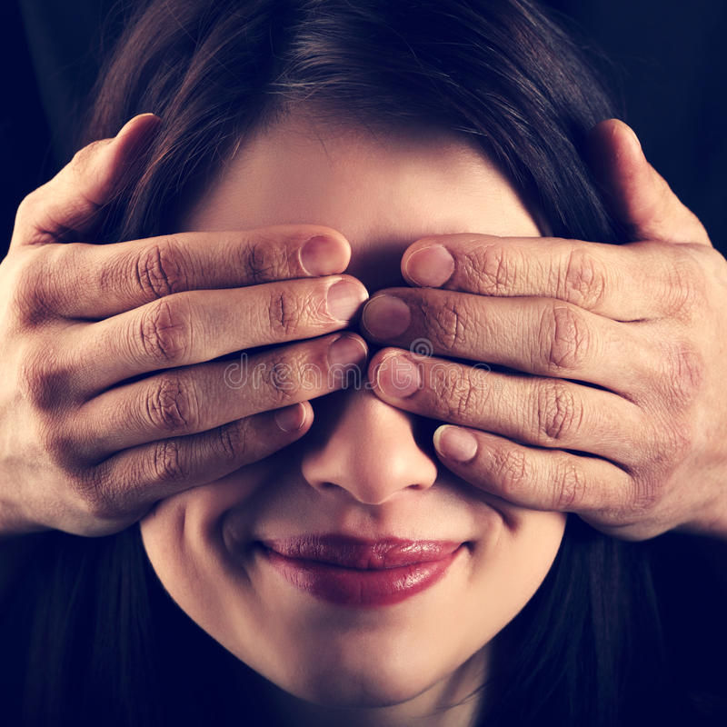 La muchacha ha cerrado al hombre de las manos de los ojos imagenes de archivo