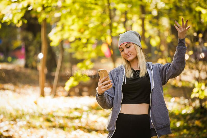 La muchacha ha perdido una señal móvil en el bosque y no puede enviar el mensaje foto de archivo libre de regalías