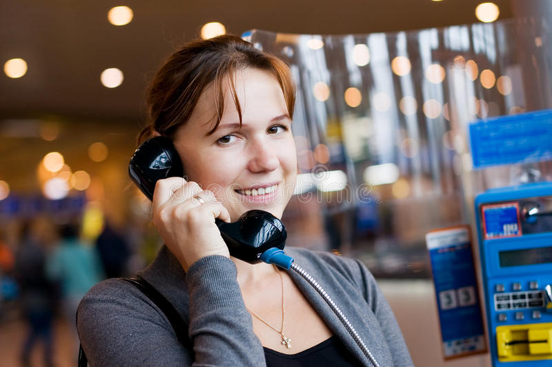 La muchacha habla por el teléfono en el aeropuerto imágenes de archivo libres de regalías