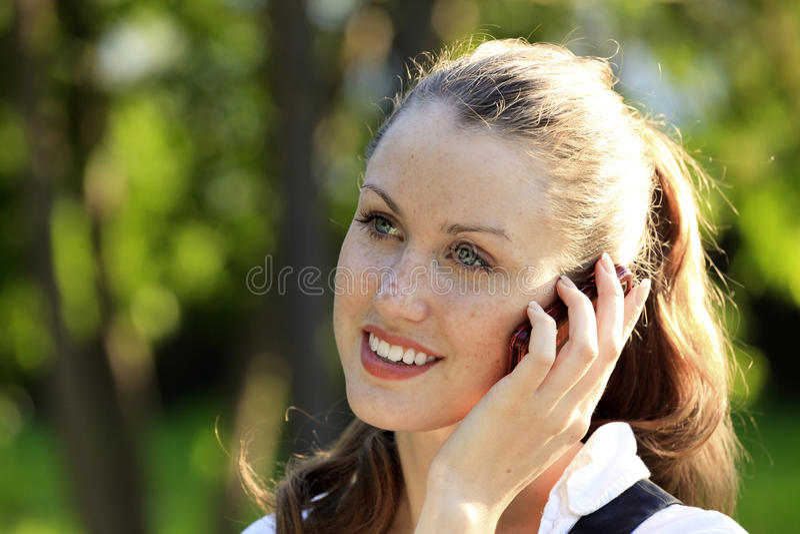La muchacha habla por el teléfono móvil fotos de archivo