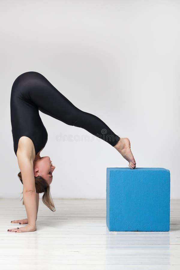 La muchacha hace el asana invertido complicado, haciendo yoga imagen de archivo