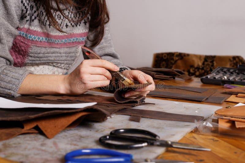 La muchacha hace el monedero de cuero imagen de archivo
