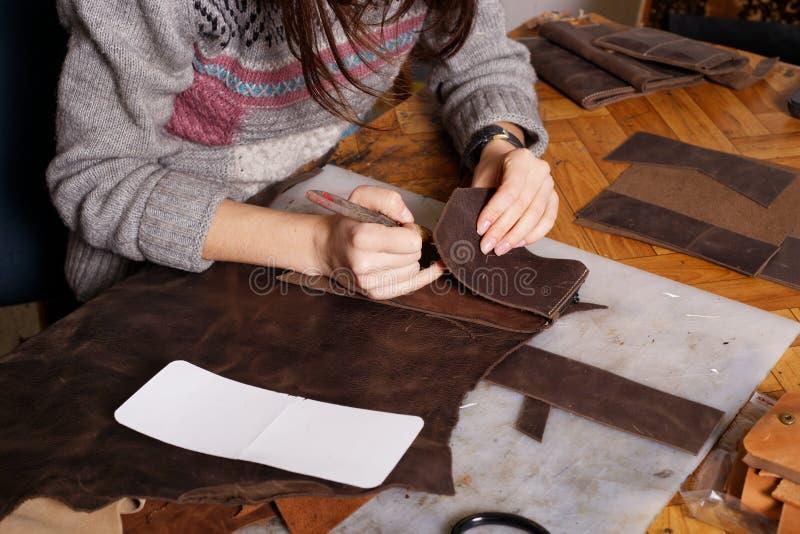 La muchacha hace el monedero de cuero fotografía de archivo