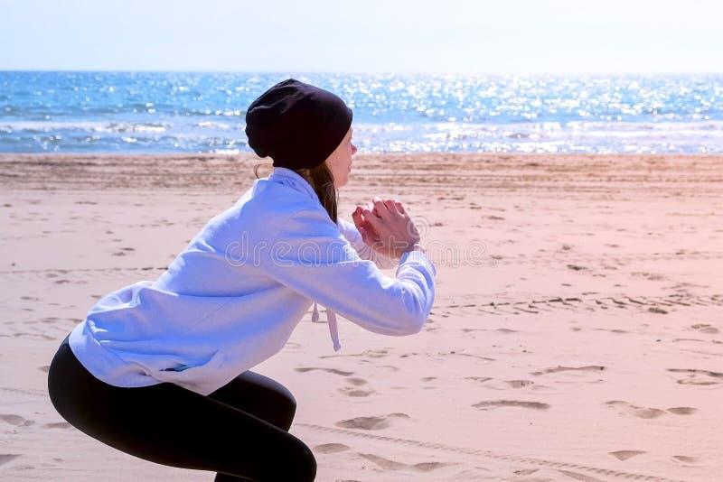 La muchacha hace posiciones en cuclillas en ejercicios del deporte al aire libre de la aptitud de la playa del arena de mar en el foto de archivo libre de regalías