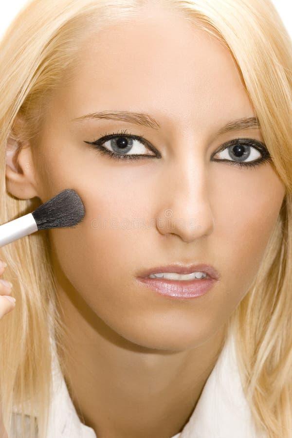 La muchacha hace su maquillaje imagen de archivo