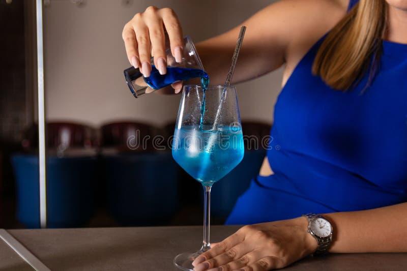 La muchacha hace un cóctel azul de la laguna en la barra en el restaurante fotografía de archivo libre de regalías