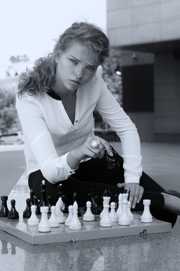 La muchacha hace un movimiento en el tablero de ajedrez foto de archivo