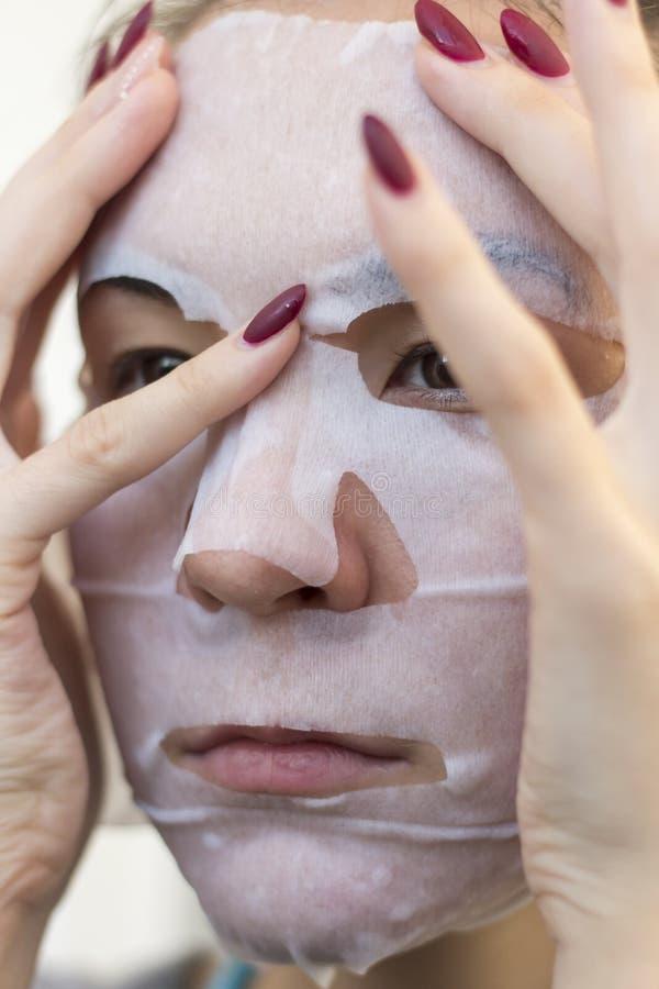 La muchacha hace una máscara de la tela imagen de archivo