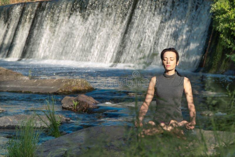 La muchacha hace yoga en el fondo de una cascada fotografía de archivo