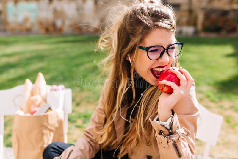 La muchacha hambrienta divertida con apetito arranca con los dientes la manzana roja que se sienta en el parque después de un via fotos de archivo