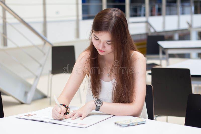 La muchacha hermosa adulta tailandesa escribe un libro que se sienta en universidad foto de archivo