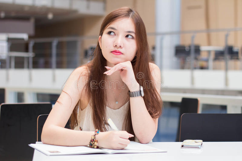 La muchacha hermosa adulta tailandesa escribe un libro que se sienta en universidad imagen de archivo libre de regalías