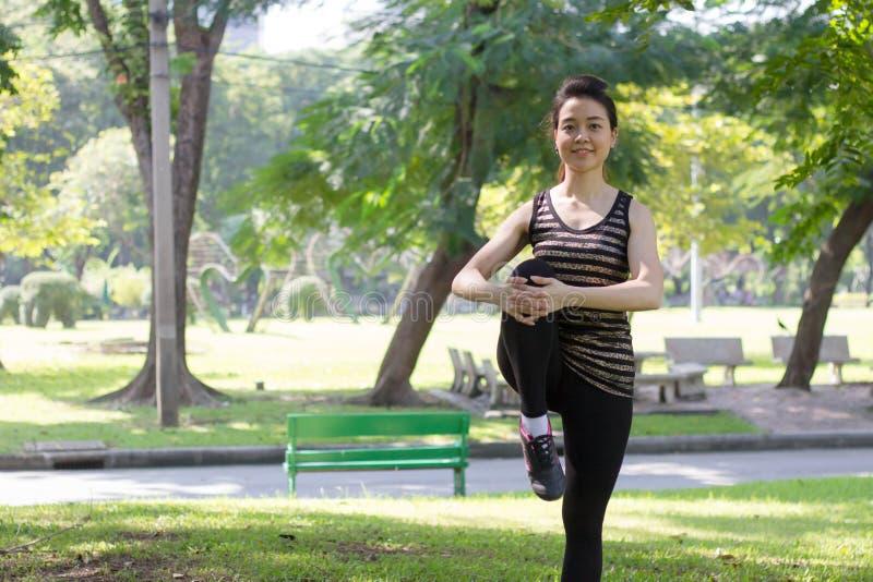 La muchacha hermosa adulta tailandesa que hace yoga ejercita en el parque fotos de archivo libres de regalías