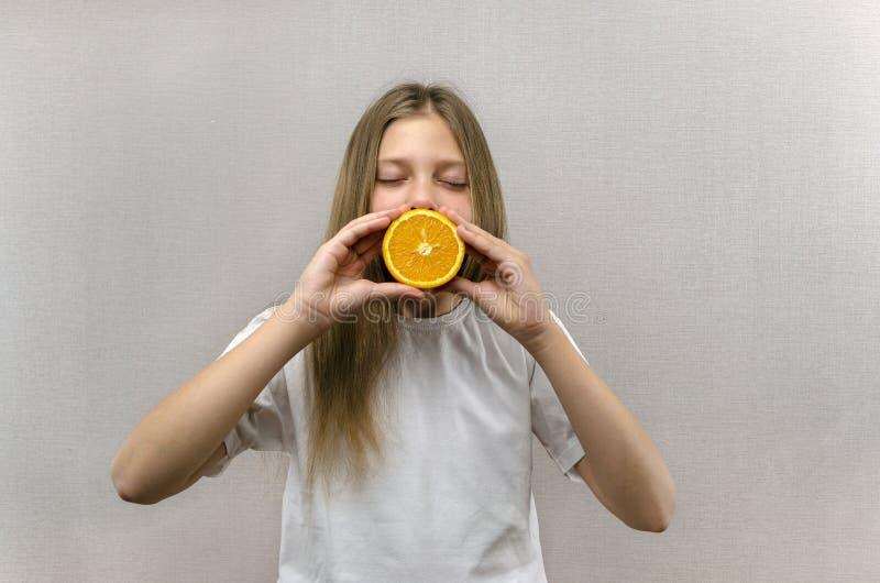 La muchacha hermosa alegre se sostiene por la mitad de mitades anaranjadas Emociones positivas Alimento sano Veggie y vegano fotos de archivo