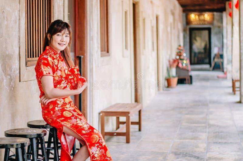 La muchacha hermosa asiática joven en la presentación roja tradicional china de la sonrisa del vestido se sienta en la silla, en  imagen de archivo