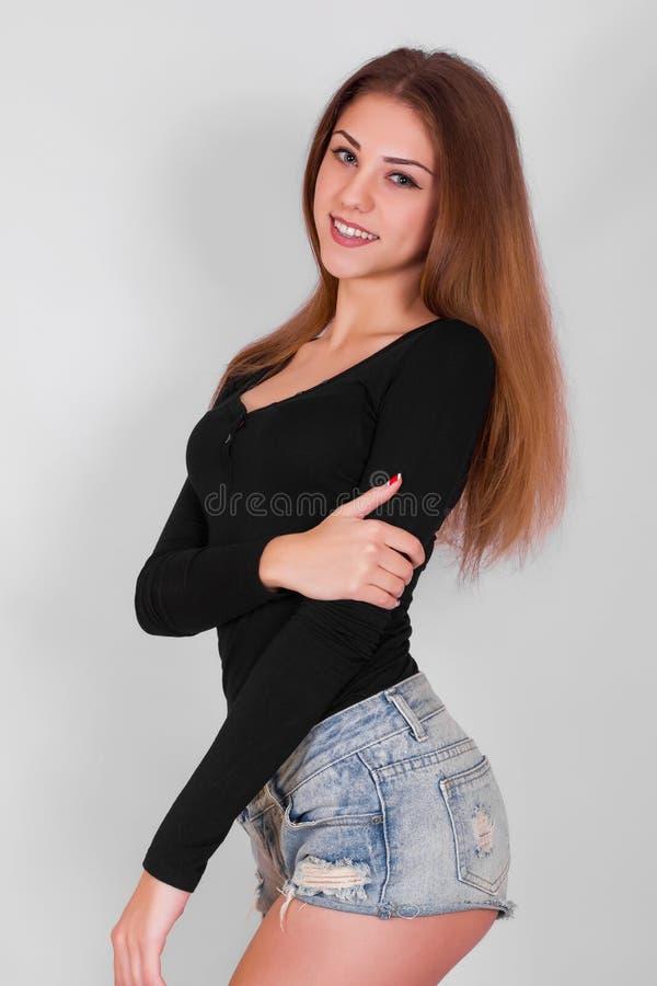 La muchacha hermosa, atractiva, rubia con el pelo largo en un fondo gris con los ojos se cerró imagen de archivo