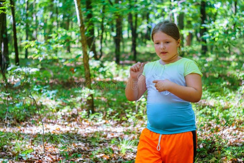 La muchacha hermosa bebe el agua de la botella, contra el verde del parque del verano imagenes de archivo
