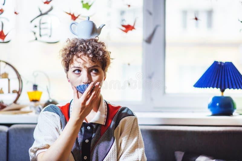 La muchacha hermosa bebe té con una tetera en su cabeza imagen de archivo libre de regalías