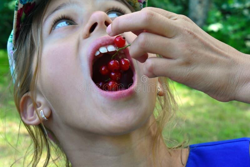 La muchacha hermosa come bayas frescas rojas Cierre para arriba imagenes de archivo