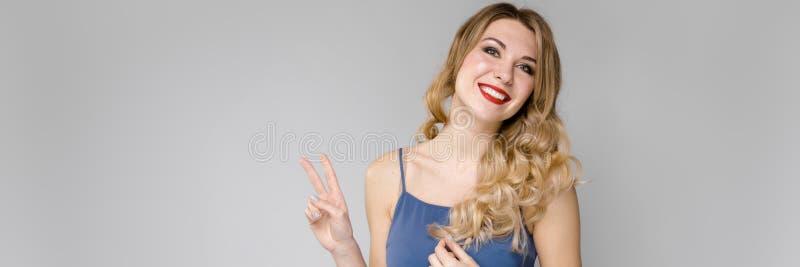 La muchacha hermosa con el pelo fuerte muestra dos fingeres Muchacha en un top azul en fondo gris foto de archivo