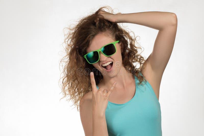 La muchacha hermosa con el pelo rizado y en gafas de sol muestra un th de la muestra fotos de archivo libres de regalías