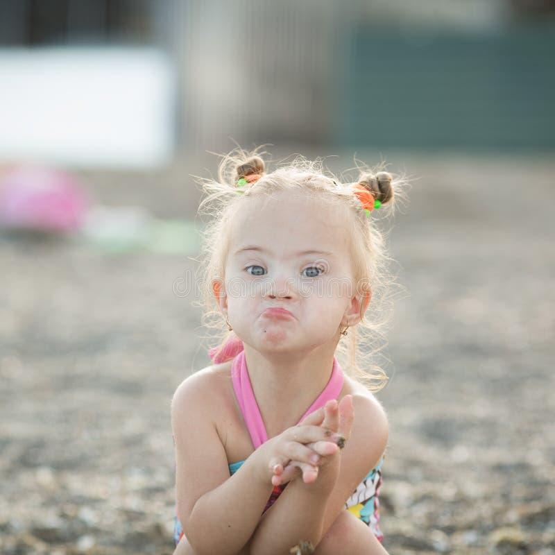La muchacha hermosa con Síndrome de Down hace un beso fotografía de archivo
