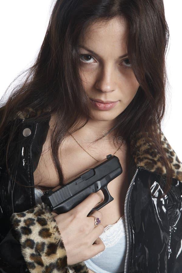 La muchacha hermosa con una pistola foto de archivo