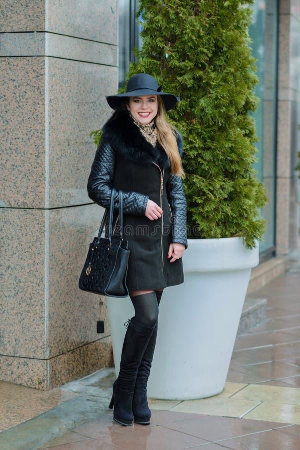 La muchacha hermosa con una sonrisa en el sombrero camina alrededor de la ciudad foto de archivo libre de regalías