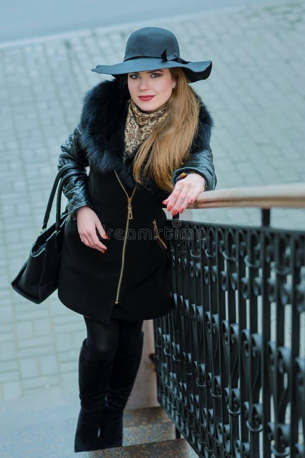 La muchacha hermosa con una sonrisa en el sombrero camina alrededor de la ciudad imagen de archivo